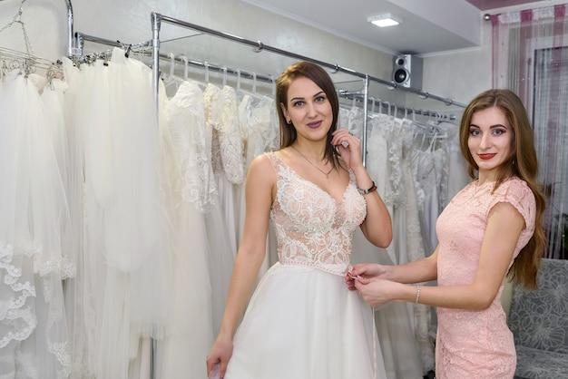 Sprzedawca pomaga pannie młodej w sukni ślubnej w butiku