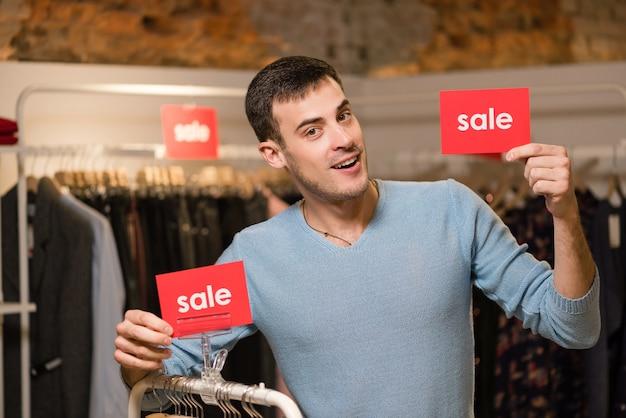 Sprzedawca posiada dwa czerwone znaki ze słowem sprzedaży