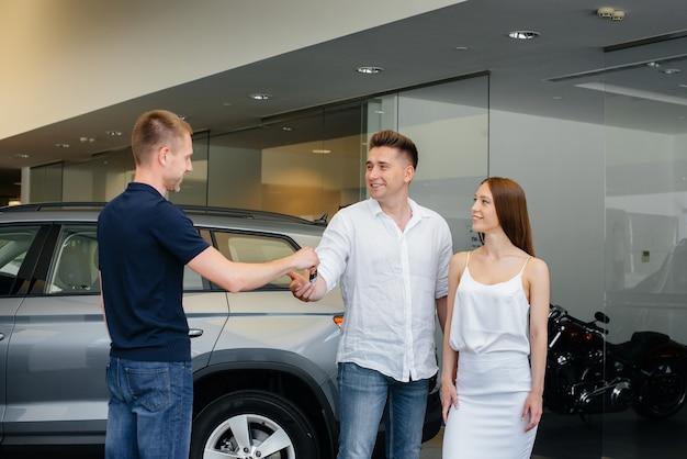 Sprzedawca przekazuje kluczyki do nowego samochodu młodej rodzinie. kupno nowego samochodu.