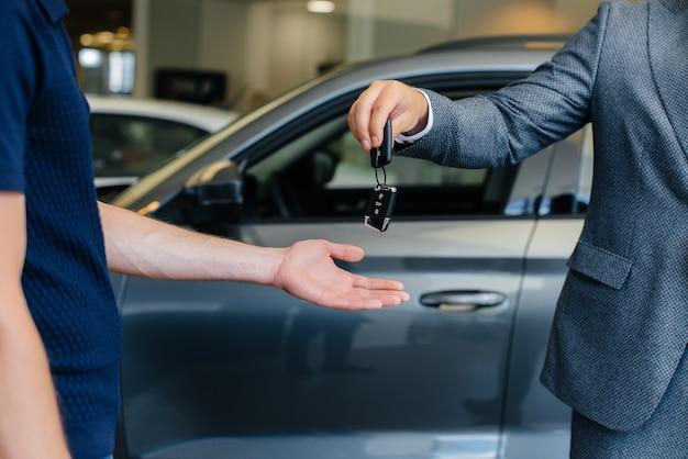 Sprzedawca przekazuje kluczyki do nowego samochodu młodej rodzinie