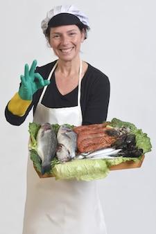 Sprzedawca ryb pokazujący talerz z rybami i owocami morza i robiący ok znak na białym tle.