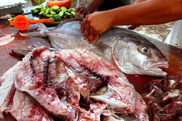 Sprzedawca ryb przygotowujący filet z ryby amberjack