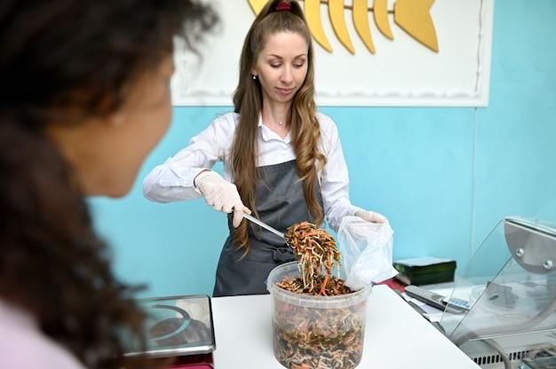 Sprzedawca ryb w sklepie z owocami morza wypełniający paczkę gotowanymi z różnymi przyprawami słone wodorosty, laminarię, sprzedaż do klienta. sprzedaż detaliczna owoców morza