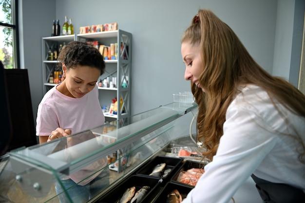 Sprzedawca ryb za ladą obsługujący kupującego w sklepie z owocami morza.