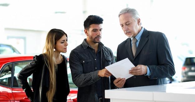 Sprzedawca samochodów czyta umowę z parą w salonie samochodowym