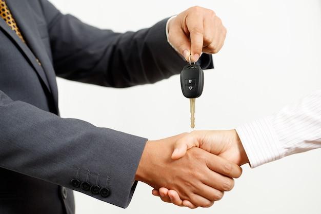 Sprzedawca samochodów dostarcza kluczyki do klientów w salonie.