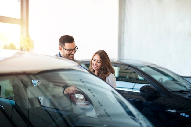 Sprzedawca samochodów i klient sprawdzający specyfikacje samochodów w salonie samochodowym.