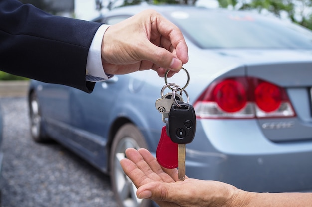 Sprzedawca samochodów i klucz do nowego właściciela.