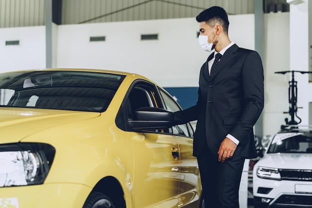 Sprzedawca samochodów mężczyzna nosi ochronną maskę medyczną na swoim miejscu pracy