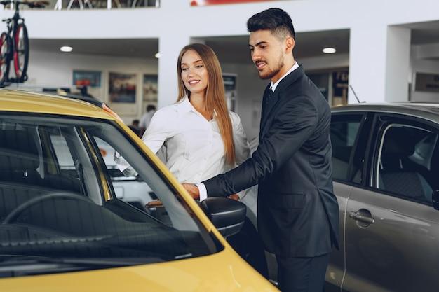 Sprzedawca samochodów mężczyzna pokazuje kobiecie nabywcy nowy samochód