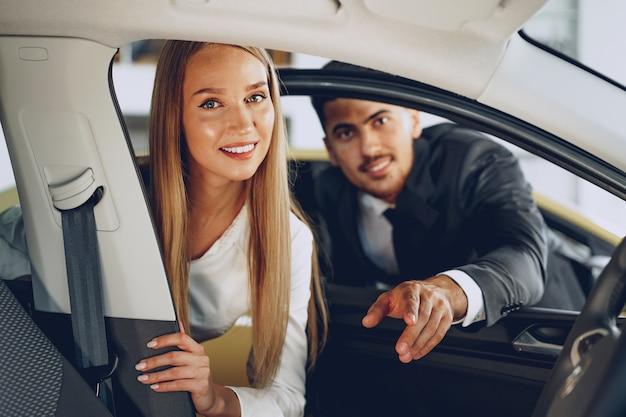 Sprzedawca samochodów mężczyzna pokazuje kupującej kobiecie nowy samochód w salonie samochodowym