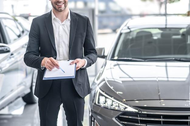 Sprzedawca samochodow. mężczyzna w garniturze z dokumentami i długopisem w dłoniach stojący w pobliżu samochodu w salonie samochodowym