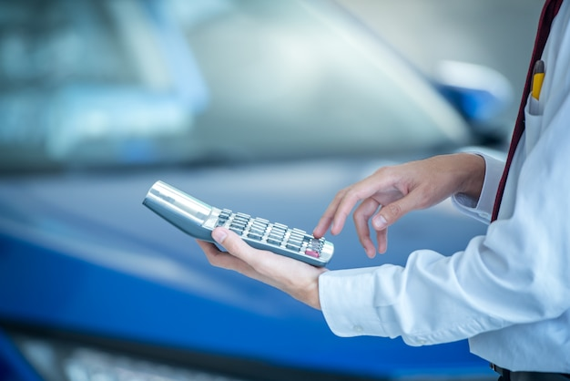 Sprzedawca samochodów naciskając kalkulator dla finansów firmy na salon samochodowy nowy niebieski samochód rozmyte tło. dla motoryzacji lub transportu