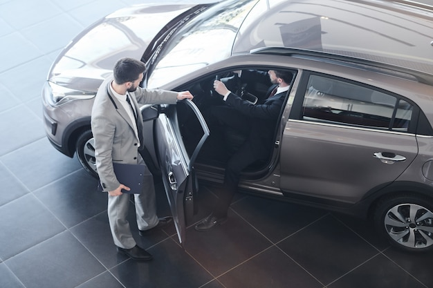 Sprzedawca samochodów otwiera drzwi do klienta