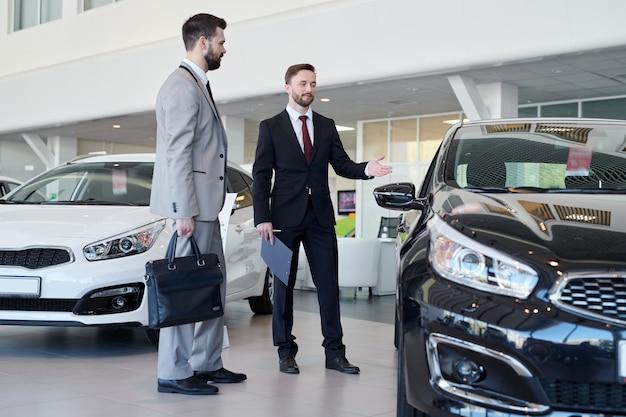 Sprzedawca samochodów pomaga klientowi