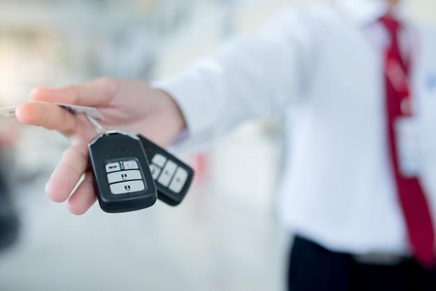 Sprzedawca samochodów przekazuje nowe kluczyki do samochodu