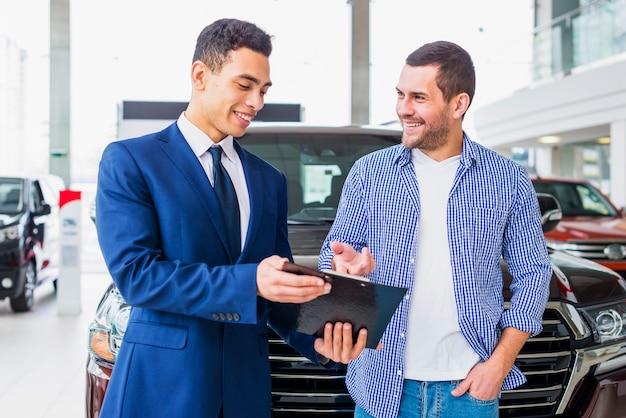 Sprzedawca samochodów rozmawia z klientem