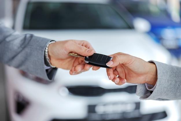 Sprzedawca samochodów wręczający kluczyki do samochodu klientowi stojąc w salonie samochodowym.