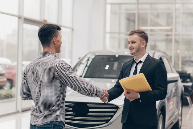 Sprzedawca samochodów współpracujący z klientem w salonie