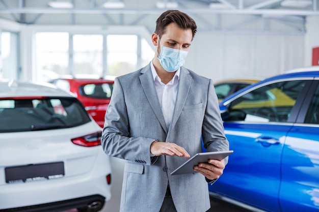 Sprzedawca samochodów z maską na twarz na stojąco w salonie samochodowym i za pomocą tabletu do sprawdzania piwa online