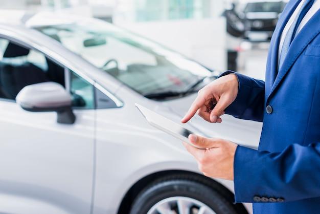 Sprzedawca samochodów z tabletem