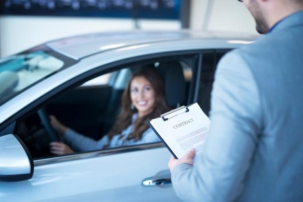 Sprzedawca samochodów z umową stoi przy nowym samochodzie, podczas gdy klient siedzi w nowym pojeździe.