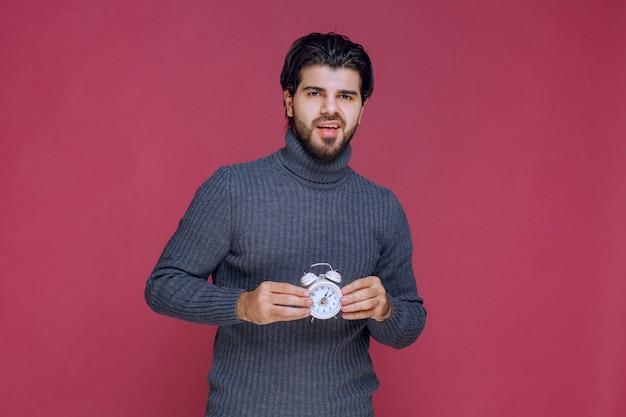 Sprzedawca trzymający biały budzik i promujący go klientowi.