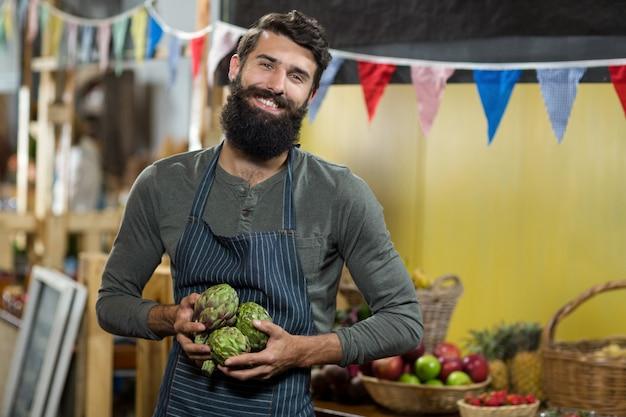 Sprzedawca trzymający krem jabłkowy w sklepie spożywczym
