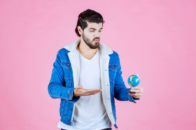 Sprzedawca trzymający mini globus i promujący produkt