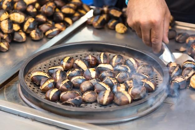 Sprzedawca uliczny sprzedaje świeżo upieczone kasztany w stambule w turcji.