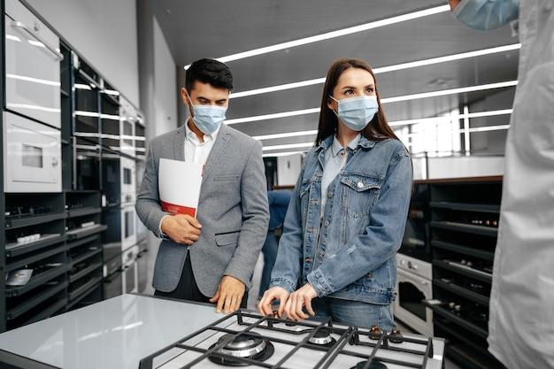 Sprzedawca w hipermarkecie pokazuje młodej parze nowy model kuchenki gazowej