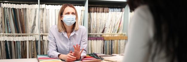 Sprzedawca w masce medycznej doradza klientowi bezpieczną obsługę w koncepcji pandemii koronawirusa