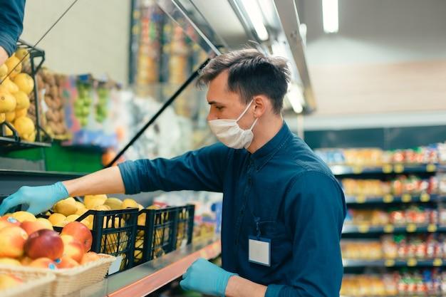 Sprzedawca w masce ochronnej stojącej przed ladą z owocami. koronawirus w mieście