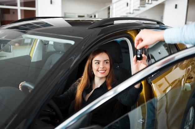 Sprzedawca w salonie samochodowym daje klientowi kluczyk