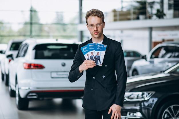 Sprzedawca w salonie samochodowym z ulotkami biznesowymi