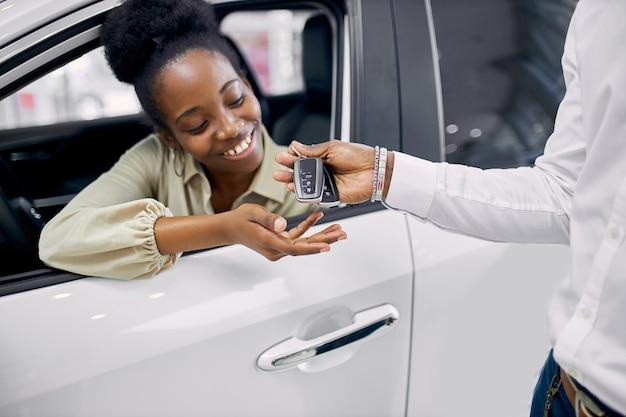 Sprzedawca w salonie wręcza długo oczekiwane klucze czarnej kobiecie siedzącej w samochodzie