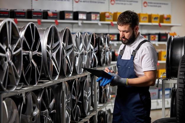 Sprzedawca w sklepie samochodowym robi notatki, sprawdza dokument i bada cechy, patrząc na stojak z felgami samochodowymi