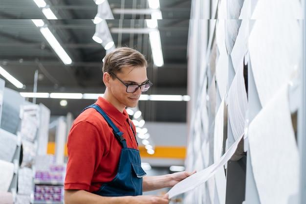 Sprzedawca w sklepie z okładzinami ściennymi sprawdzający oznaczenia na tapecie