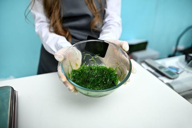 Sprzedawca w sklepie z owocami morza trzyma na wyciągniętych dłoniach szklaną miskę z zielonymi wodorostami. sprzedaż detaliczna owoców morza