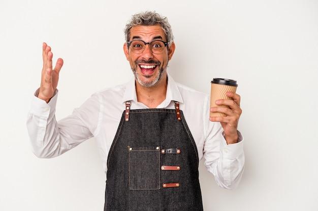 Sprzedawca w średnim wieku trzymający kawę na wynos na białym tle odbiera miłą niespodziankę, podekscytowany i podnosząc ręce.