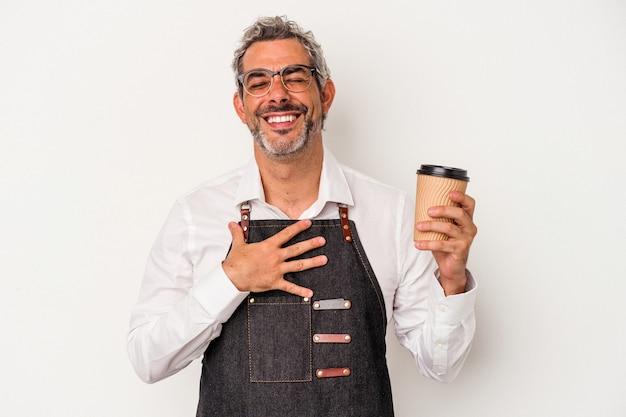 Sprzedawca w średnim wieku trzymający kawę na wynos na białym tle śmieje się głośno trzymając rękę na klatce piersiowej.