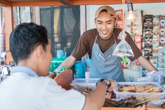 Sprzedawca z angkringa uśmiecha się, obsługując klientów przy stoisku z wózkami