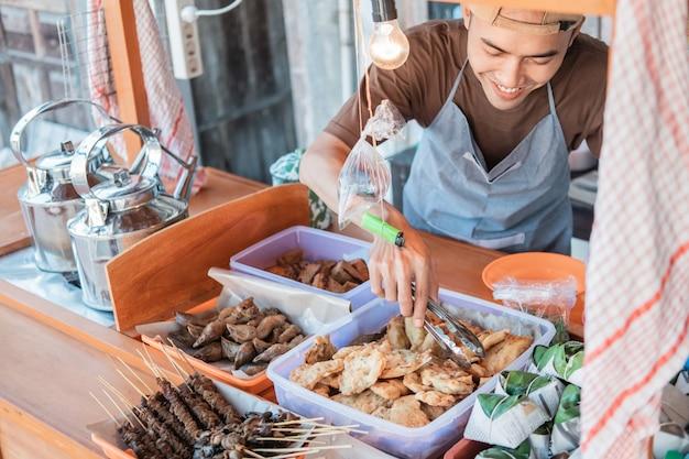 Sprzedawca z wózkami uśmiechnął się, trzymając szczypce z jedzeniem, żeby posprzątać ekspozycje z jedzeniem na straganie