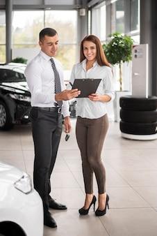 Sprzedawcy dealerów samochodowych sprawdzający ofertę