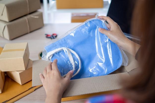 Sprzedawcy internetowi pakują torbę do pudełka, aby dostarczyć produkt kupującemu, który zamówił na stronie internetowej