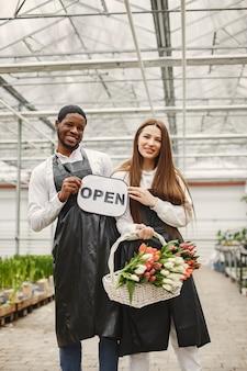 Sprzedawcy kwiatów ze znakiem. ogrodnicy w fartuchach. wiele tulipanów w szklarni.