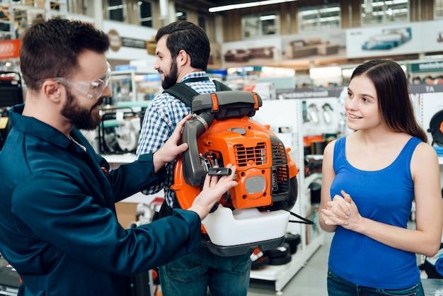 Sprzedawcy pokazujący klientom dmuchawę do liści przemysłowych