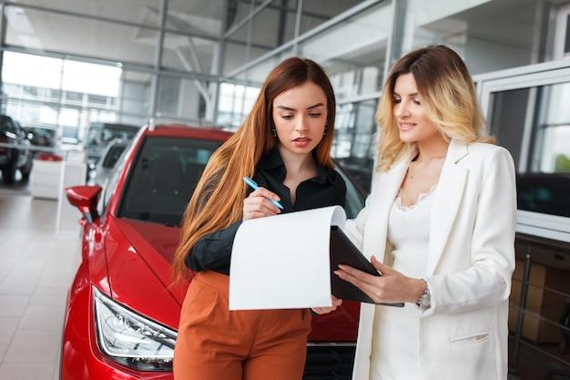 Sprzedawczyni daje dokumenty do podpisania dla klientki