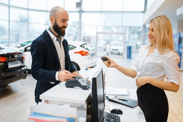 Sprzedawczyni daje klucze od nowego samochodu mężczyźnie w salonie samochodowym. klient i sprzedawczyni w salonie samochodowym, mężczyzna kupujący transport, firma dealera samochodowego