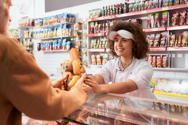 Sprzedawczyni kobieta daje kiełbasy starszemu mężczyźnie.